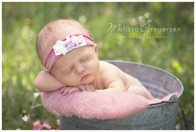 Newborn in metal bucket in natural outdoor setting.