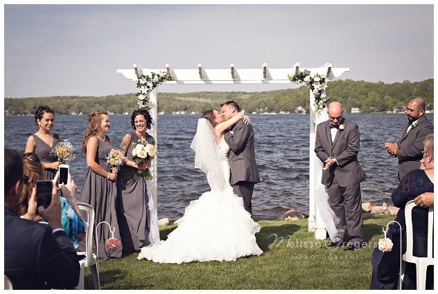 First kiss and husband and wife at the wedding ceremony at Bay Pointe Inn on Gun Lake photographed by Melissa Gregersen Photography