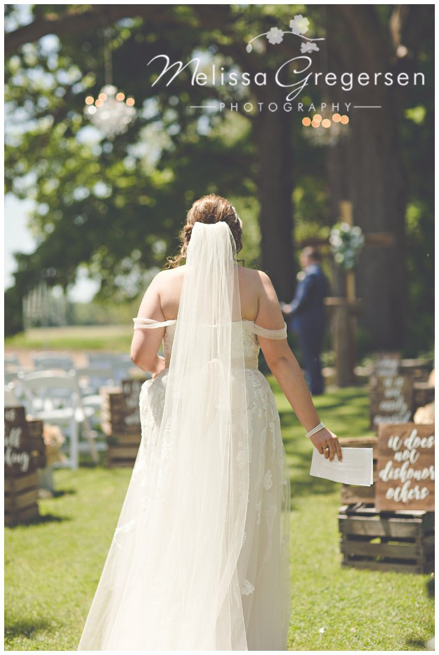 Beautiful bride walking to her groom for the first look at the ceremony site at the vintage rose barn