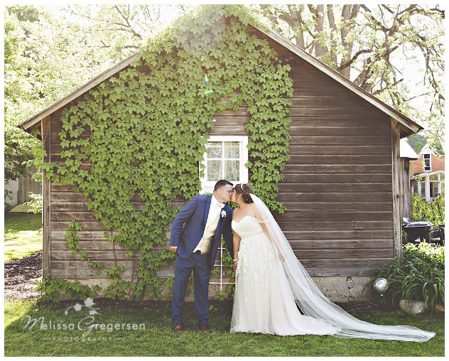 Bride and groom kissing in front of rustic old barn