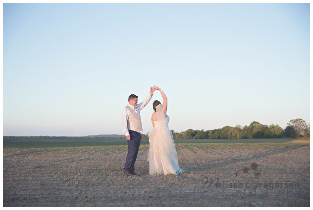 Bride and Groom dancing at sunset on their wedding day in a corn field