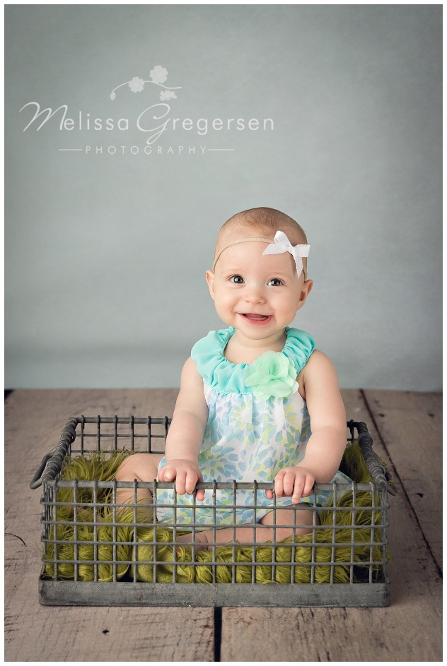 Six month baby girl sitting in basket wearing blues and greens in studio baby photography