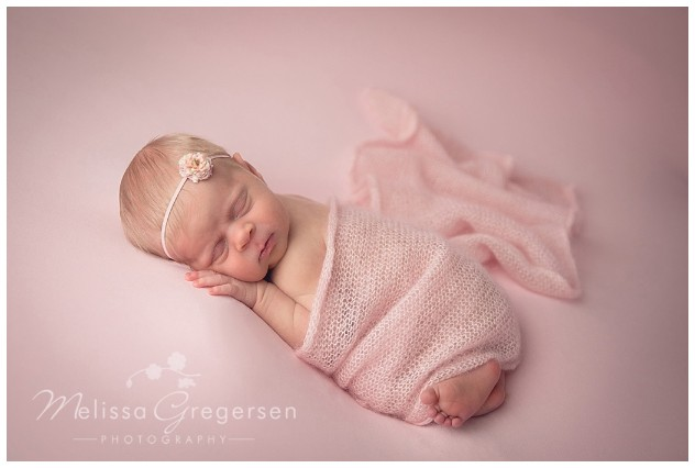 Newborn in all soft pink wrap.