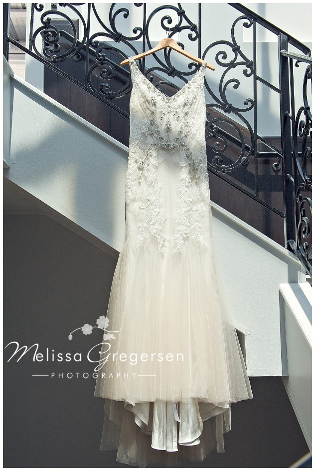 Gorgeous bridal gown hanging in staircase.
