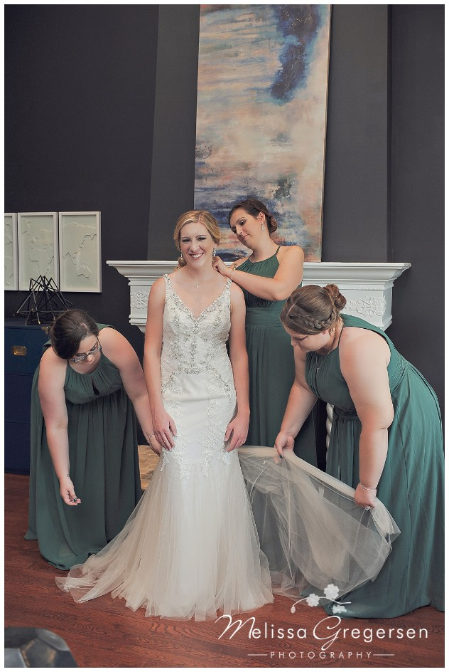 Cutest bride with her bridesmaids helping her with finishing touches