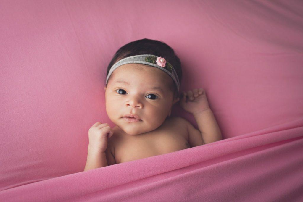 Newborn baby girl lying on pink blanket with eyes open