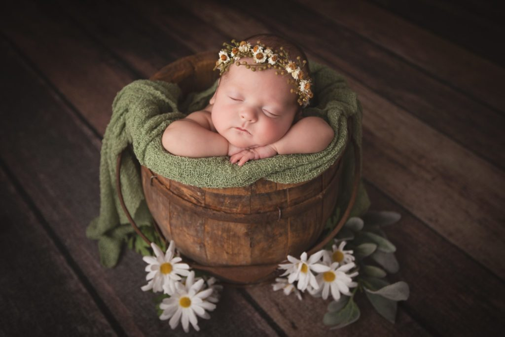 Newborn baby girl photographed in a wooden bucket with daisy floral crown