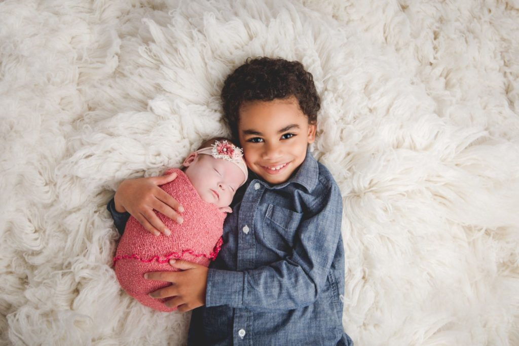 Big brother holding his newborn baby sister for a photograph