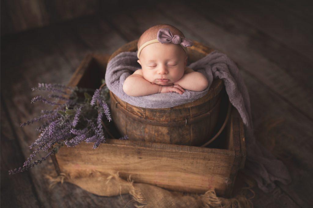 newborn baby in wooden bucket with lavender at Gregersen Photography Studio