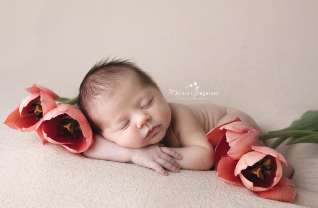 newborn baby girl lying on bed with fresh tulips