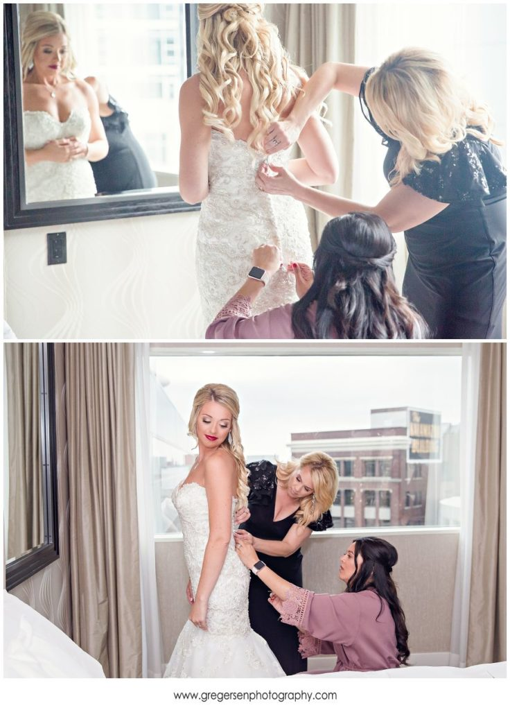 bride getting her wedding dress on with her mom