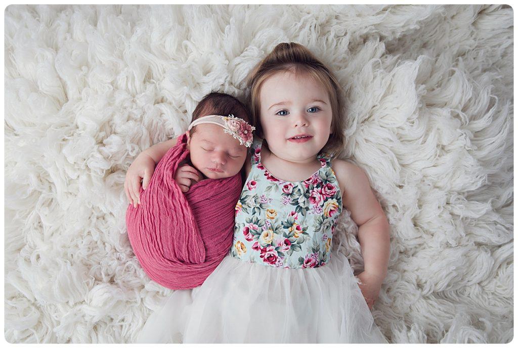 Newborn baby girl with big sister photographer on white fur rug