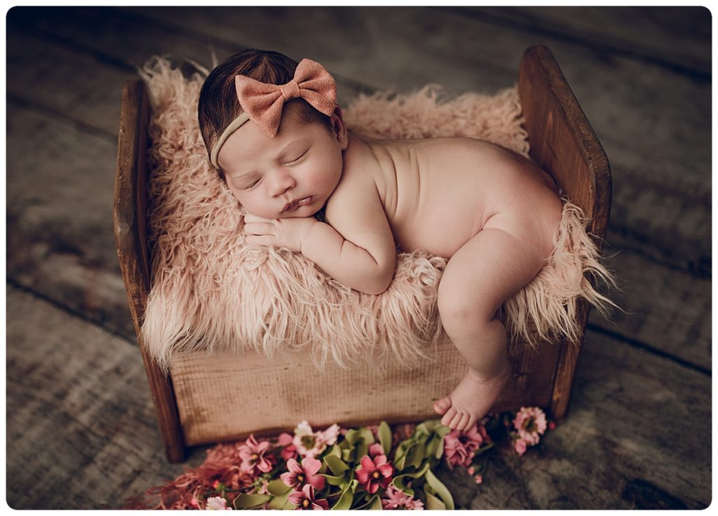 Newborn Baby girl photographed in a wooden bed at Gregersen Photography
