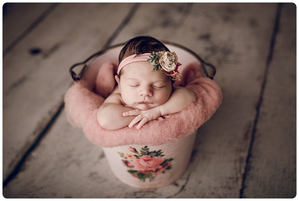 Newborn baby girl photographed in a pink floral metal bucket