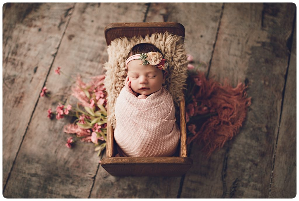 Newborn baby girl photography in wooden bed with pink flowers