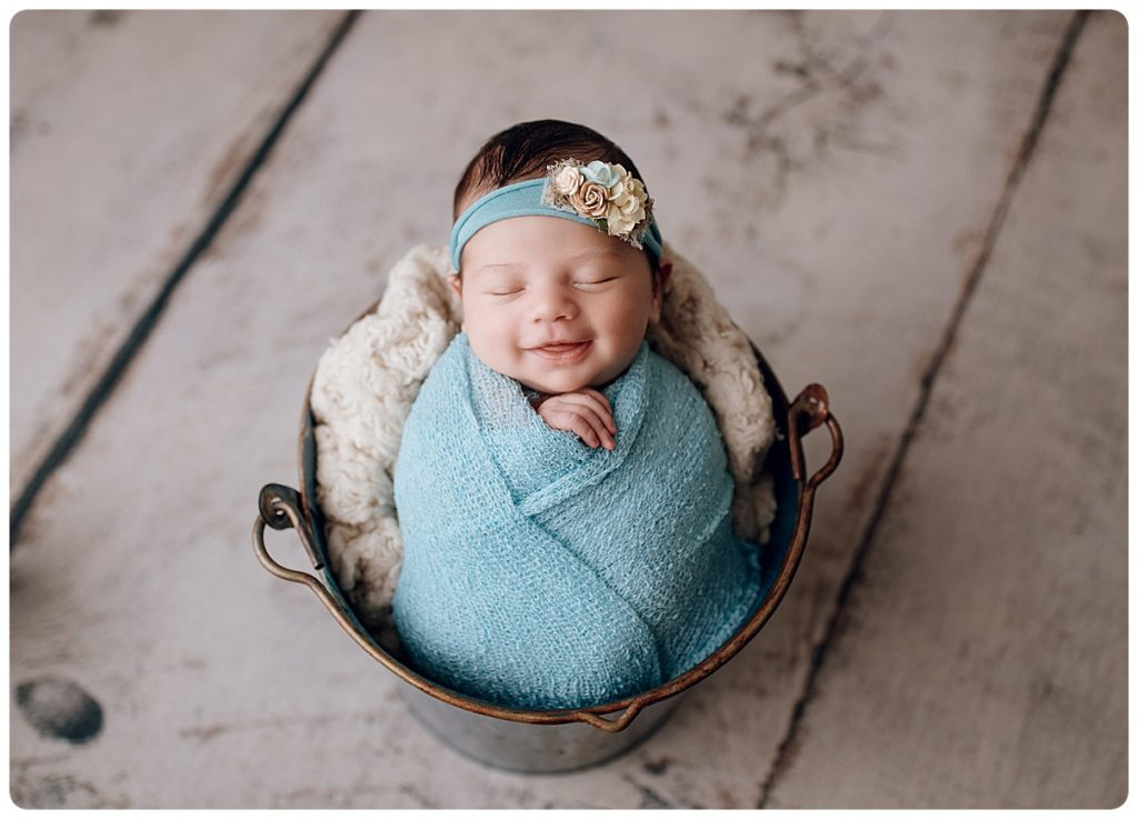 Newborn baby girl photographed in a bucket at gregersen photography