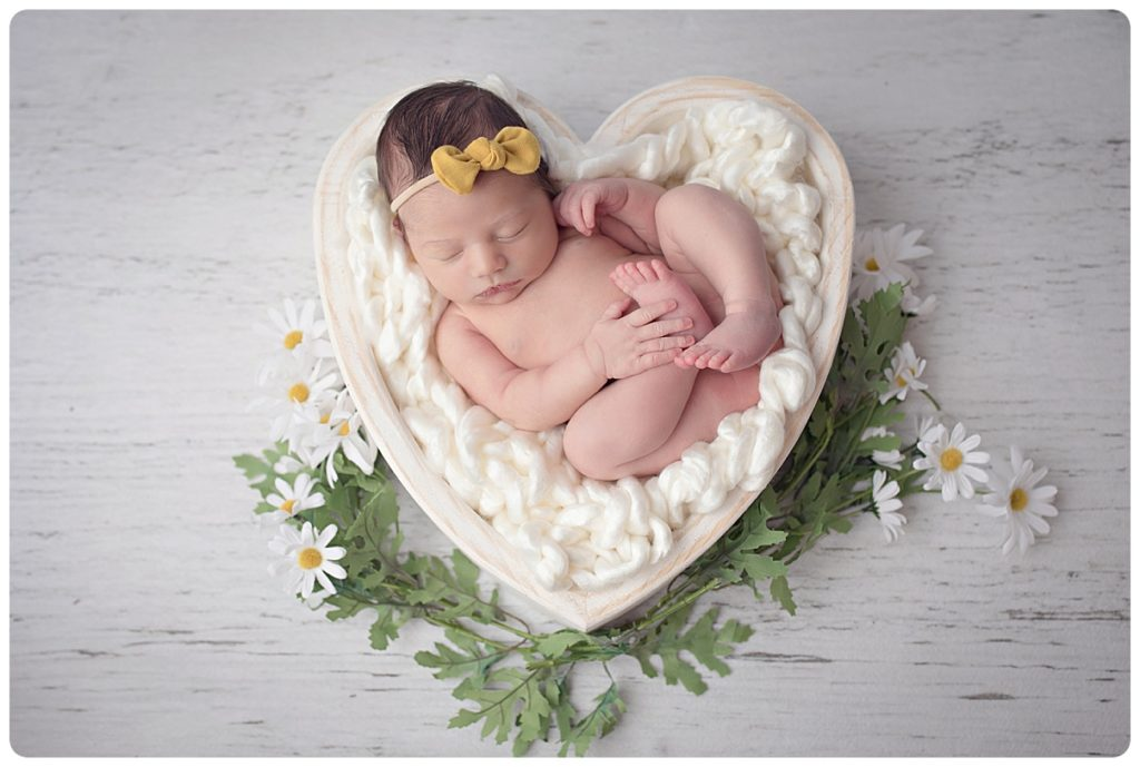 Newborn baby girl photographed in a white heart bowl with daisy flowers