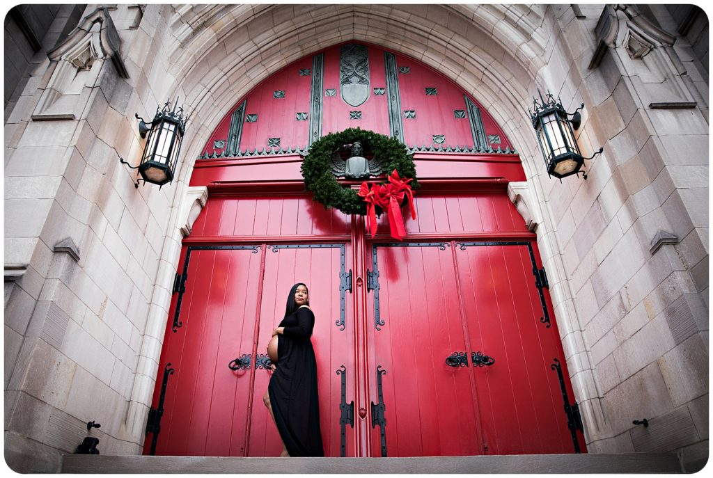 Pregnant lady poses in Kalamazoo Michigan for photography session in front of red door.
