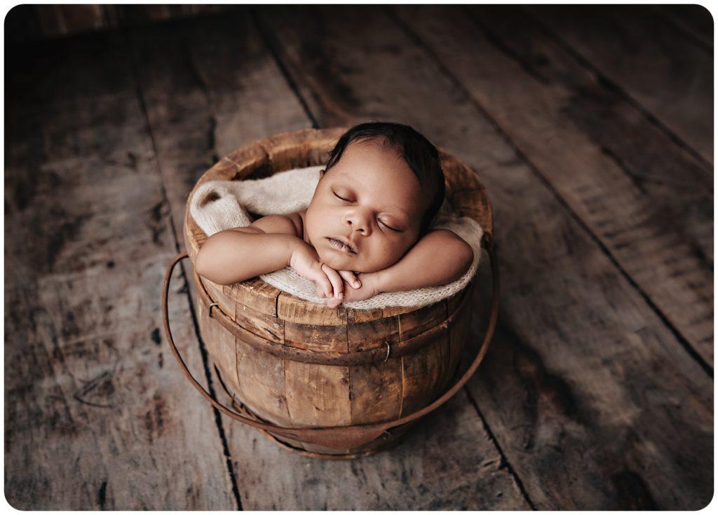 Newborn baby boy in a vintage wooden bucket