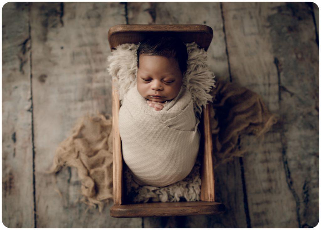 Newborn baby boy in a wooden bed.