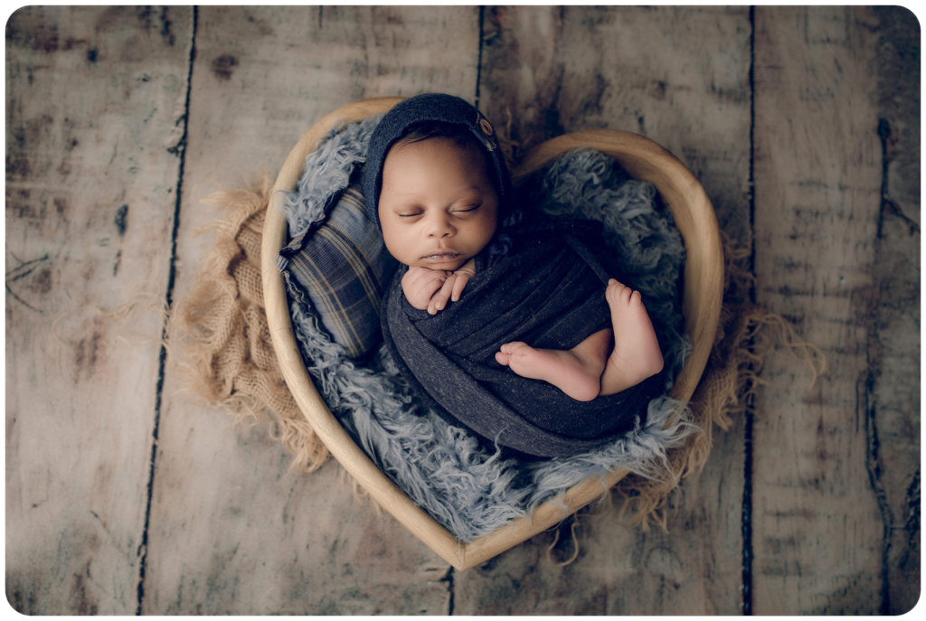 Newborn baby boy in a wooden heart bowl