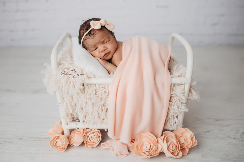 Newborn baby girl lying in white bed with flowers at Gregersen Photography Studio in Kalamazoo, MI