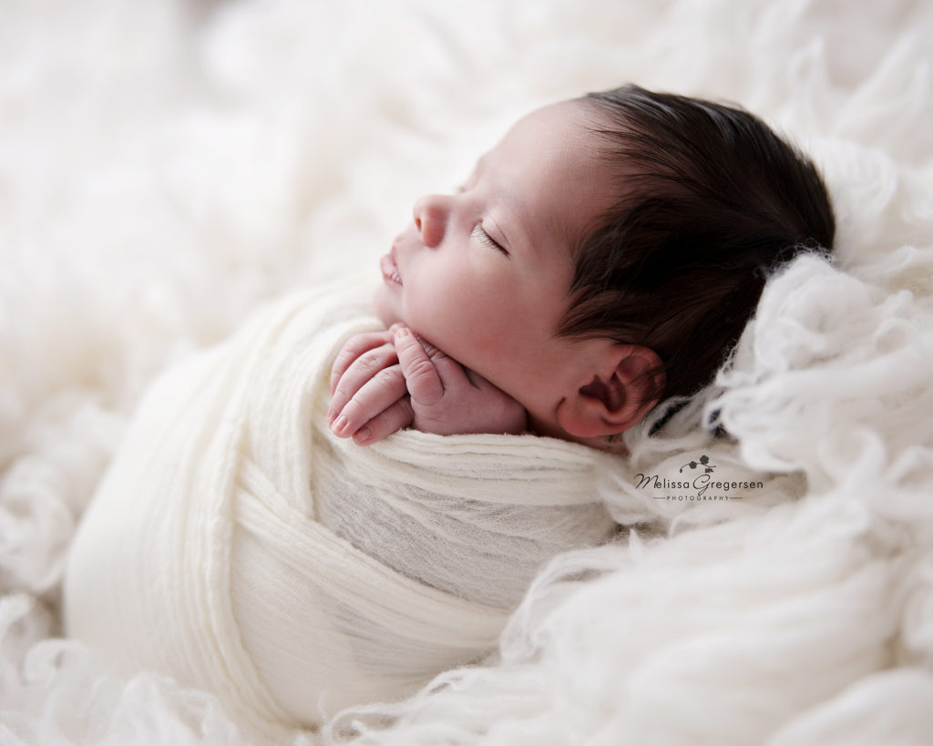 Newborn baby wrapped up lying on a fur at Gregersen Photography Studio in Kalamazoo, MI