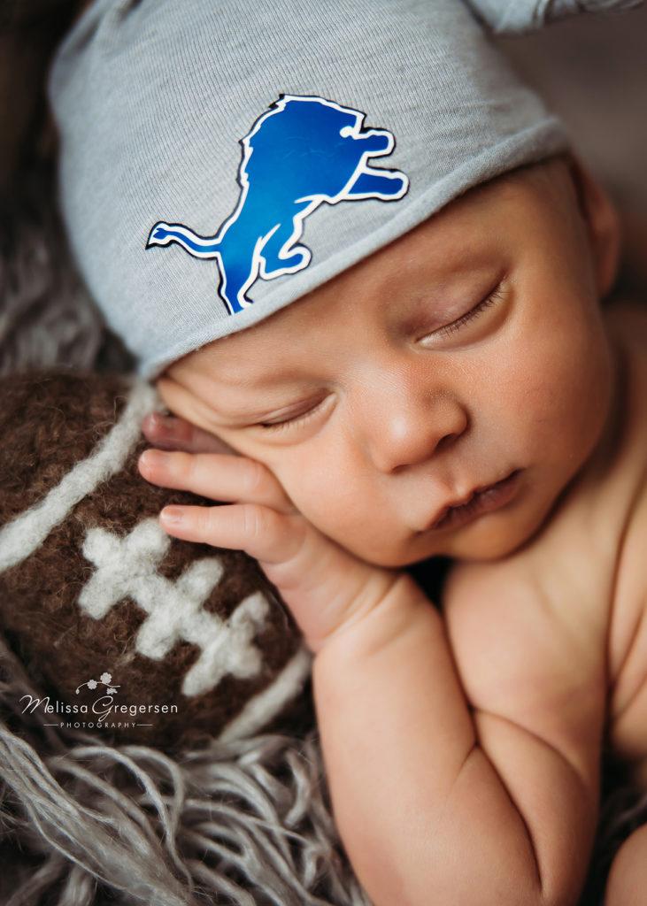 Newborn baby boy photographed with Detroit Lions cap at Gregersen Photography Studio in Kalamazoo, MI